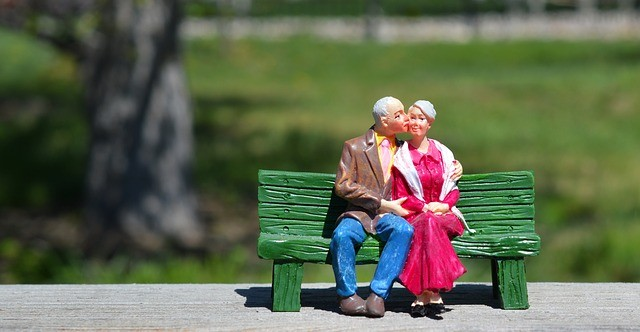 graphic of a senior couple on a park bench with the man giving a kiss to the cheek of the woman