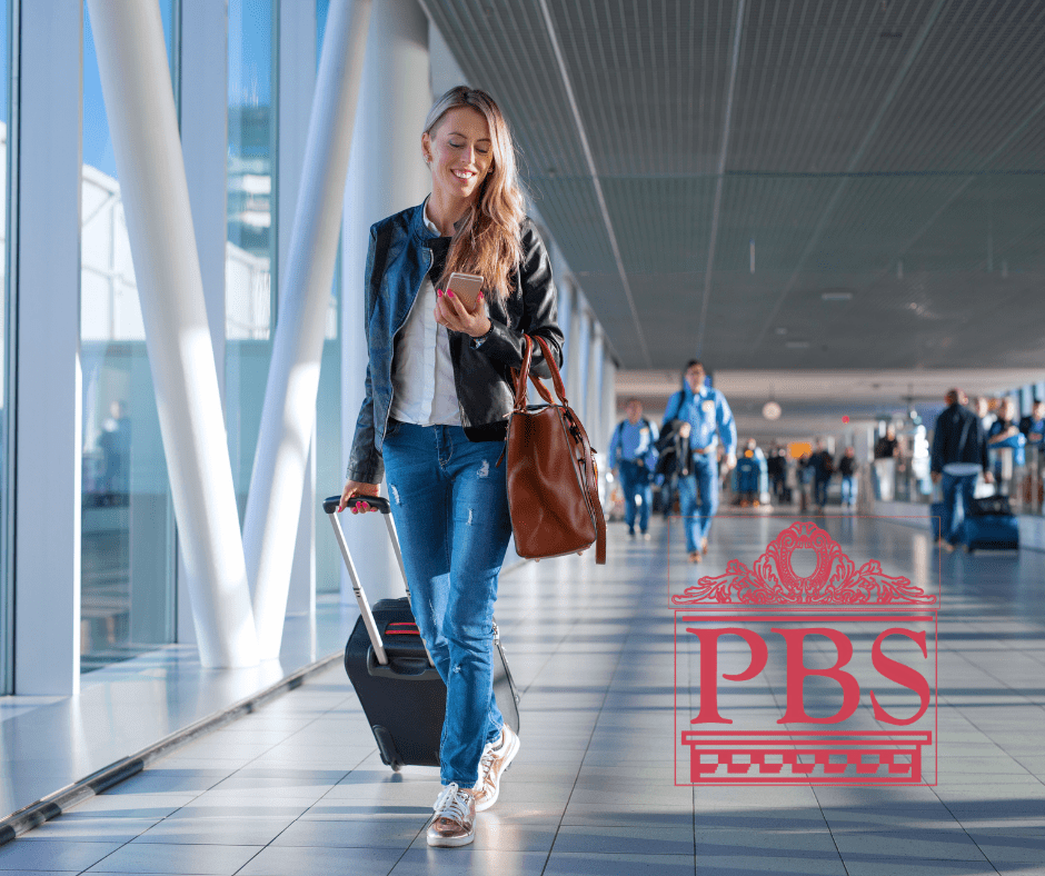 photo of woman walking through an airport dragging rolling luggage